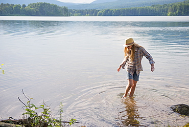 A young girl in a straw hat and shorts paddling in the shallow waters of a lake