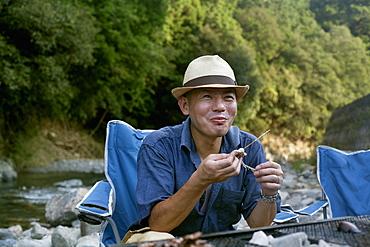 Man eating a grilled fish at a picnic, Kyoto, Honshu Island, Japan