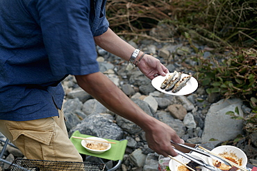 Man holding a plate of grilled fish at a picnic, Kyoto, Honshu Island, Japan