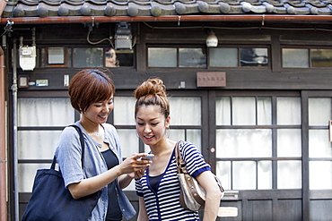 Two women standing outdoors, looking at cellphone, Osaka, Japan