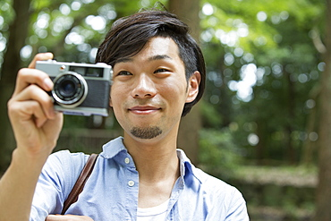 A man in a Kyoto park holding a camera, taking a picture, Kyoto, Honshu Island, Japan