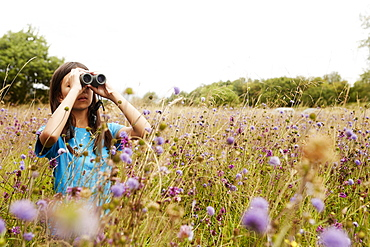 A girl holding binoculars, a young bird watcher standing in a meadow of tall grass and wild flowers, Bristol, Avon, England
