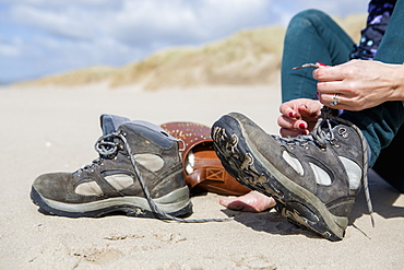 Young woman taking her hiking boots off on the beach at Harlech, Gwynedd, Wales