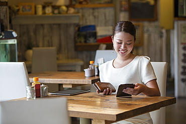 Woman sitting at a table in a cafe, holding the bill and her purse, smiling, Osaka, Japan