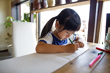 Girl with pigtails sitting at a table, drawing with felt tip pens, Osaka, Japan