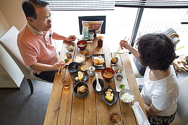 Woman and man sitting at a table, eating Japanese Food with chopsticks, Osaka, Japan