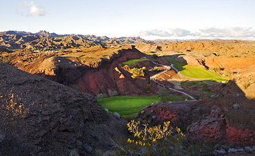 An elevated view over the mountain and desert landscape and golf course greens in the valley, Desert golf course, Arizona, USA