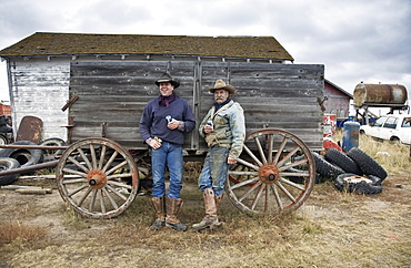 Two men in cowboy hats and cowboy boots leaning against a wooden wagonCowboys, Saskatchewan, Canada
