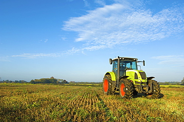 A tractor in a stubble field in GloucestershireTractor in field, Gloucestershire, England