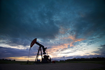 An oil derrick, a well head pump arm with frame, silhouetted against the evening sky. Oil business, Oil field pumpjack, Saskatchewan, Canada