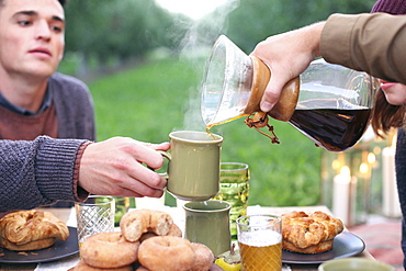 An apple orchard in Utah. Group of people sitting round a table with food and drink, pouring coffee, Sataquin, Utah, United States of America