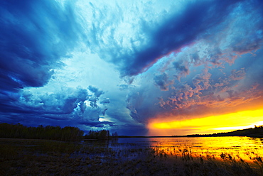 Sunset on the horizon over a lake, and storm clouds rising, Saskatchewan, Canada
