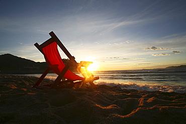 A chair on the sand facing the water, Barra de Navidad, Mexico