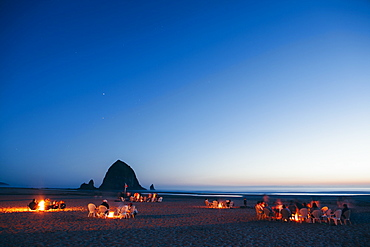Crowds of people sitting by glowing campfires on Cannon Beach at dusk, Haystack Rock in the background, Tillamook County, Oregon, USA