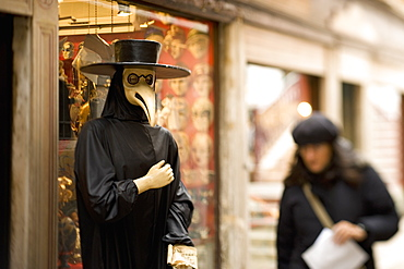 A person in a bird mask, a traditional carnival costume, with a long bird beak, A woman walking by, Venice, Italy