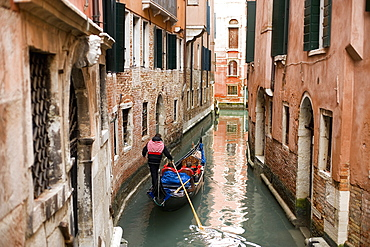 A gondola boat gliding down a small narrow waterway, between historic houses in the city of Venice, Venice, Italy