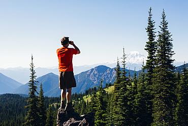 A man standing on a mountain ridge, taking a photograph of the landscape, Skamania County, Washington, USA