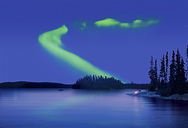 The Northern Lights in the night sky, the Aurora borealis above a calm lake, Two people by a fire on the lake shore, Canada