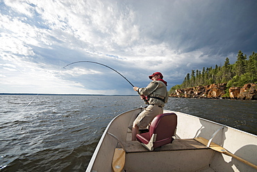 A man fishing from an open boat offshore, A fish on the line, The fishing rod bending from the weight, USA