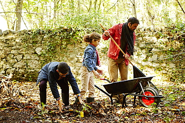 A family raking and scooping up leaves in autumn, England, United Kingdom