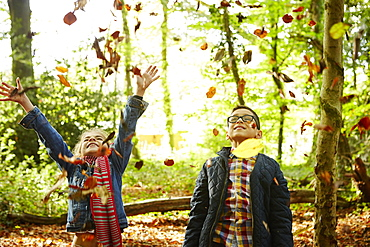 A girl and her brother throwing autumn leaves in the air, England, United Kingdom