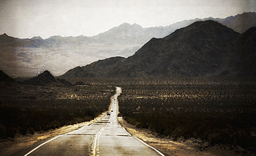A road leading into the distance, to a range of mountains. Desert scenery, cars on the road, California, United States of America