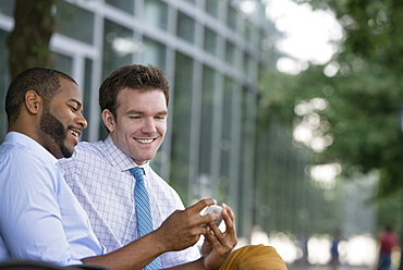 Summer in the city. Businesspeople outdoors, on the go. Two men sitting on a bench, using a smart phone.