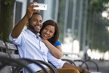 Summer in the city. Businesspeople outdoors, on the go. A couple sitting on a bench, taking a selfy photograph.