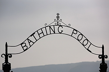 A metal arch over a gate to the Bathing Pool in a resort, Gate, Cornwall, England