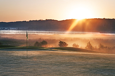 Glowing dawn light on a golf course green. The sun just appearing above a mountain range, Kenosee, Saskatchewan, Canada