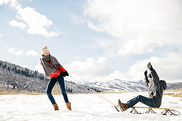A young girl pulling her brother on a sledge through the snow, Mountains, Utah, USA