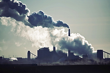 Heat, steam and smoke rising from the chimneys of a power plant against the sky, Power Plant, USA