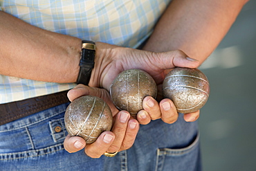 A boules player holding three metal boules in his hands behind his back, Boules player, France