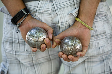 A boules player with one metal ball in each hand, held behind his back, Boules player, France