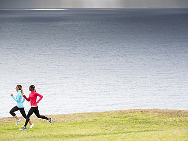 Two women jogging along the coast.