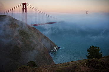 View of the Golden Gate Bridge in San Francisco at sunset in fog.