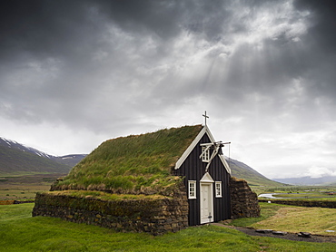 A traditional wooden church with turf roof, earth and grass material on the steep pitched roof, Iceland