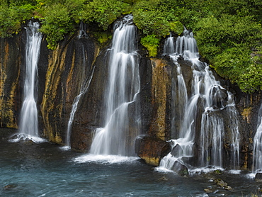 Hraunfossar waterfalls, a series of cascading torrents flowing from lava fields over a sheer cliff into the river Hvita, Iceland