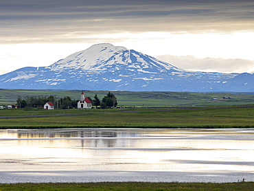A traditional church on a lake shore in a mountain landscape, Iceland