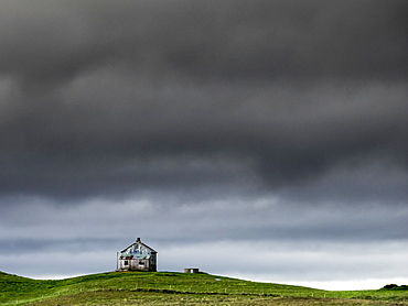 A barn on the crest of a hill, and dark storm clouds glowering over the land, Iceland