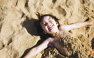 A boy lying on his back on the beach, his torso covered in sand, laughing, England