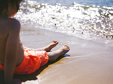 A boy sitting on the sand at the water's edge watching the waves reach the beach, England