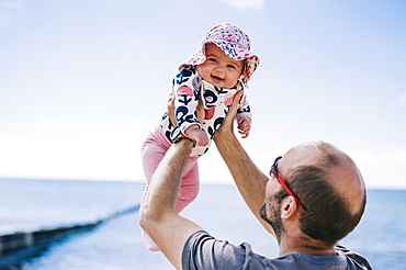 A father lifting his baby daughter in a sun bonnet up in the air, , England