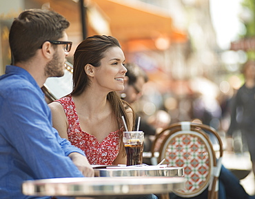 A couple sitting in seats at a pavement cafe in a city, France