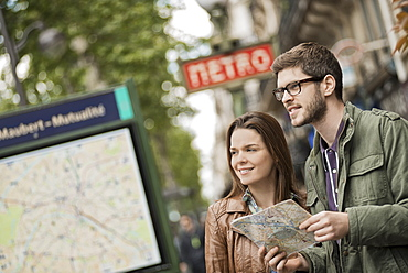 A couple using a street map beside an information sign under a metro sign in a city, France