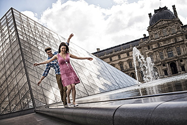 A couple in the courtyard of the Louvre museum, by the large glass pyramid. Water jets and shallow pool, France