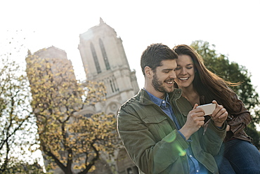A couple in a historic city, looking at a smart phone, France