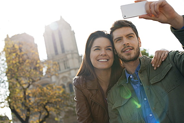 A man holding a smart phone taking a selfy of himself and his girlfriend in front of Notre Dame cathedral, France