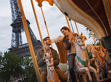 A couple, man and woman riding traditional gallopers on a carousel ride in the shadow of the Eiffel Tower in Paris, France