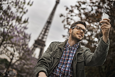 A man sitting on a park bench in the Champs de Mars under the Eiffel Tower, France